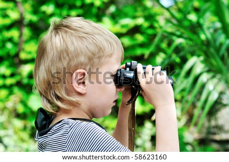 Boy looking through binocular in selective focus - stock photo