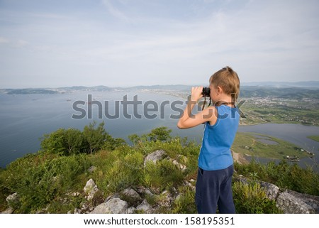 Boy looking through binoculars from the top of the mountain to the city by the sea. - stock photo