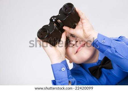 Boy looking through binoculars isolated over white - stock photo