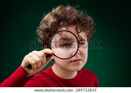 Boy looking through magnifying glass  - stock photo