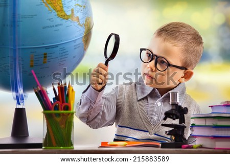 Boy looking through magnifying glass at globe, isolated on white background. School, education concept. - stock photo