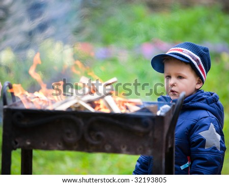 Boy looking to old style metal campfire made ready for grilling - stock photo