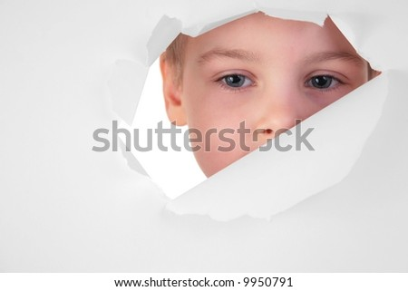 boy looks in a hole in a sheet of a paper