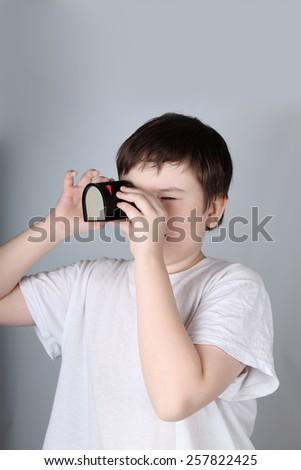Boy looks in filmoskop, light background - stock photo