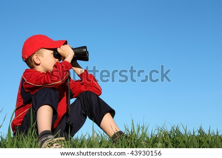 Boy looks into binoculars on top of hill - stock photo