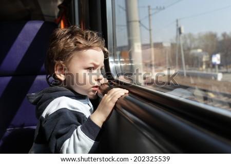 Boy looks through the window of the train - stock photo