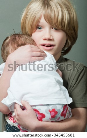 Boy lovingly holding his new born baby sister