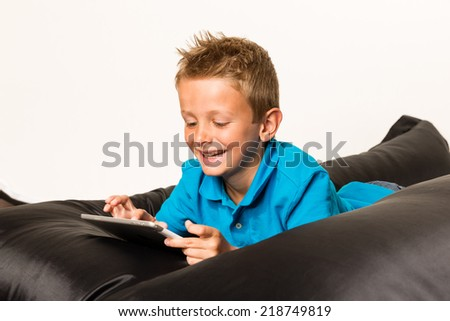 Boy lying down on beanbag with his tablet. Studio shot on white background.