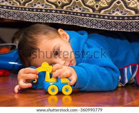 boy lying down playing with toy car - stock photo