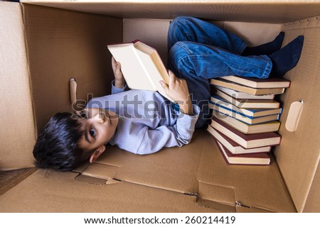 boy lying in a cardboard box and reading a book - stock photo