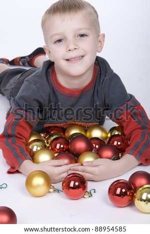 boy lying on a white floor, surrounded by Christmas decorations