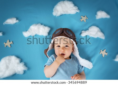 boy lying on blanket with white clouds in pilot hat - stock photo