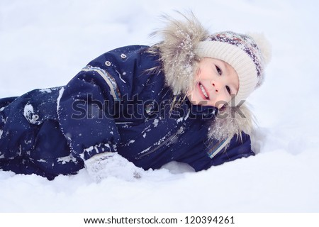 Boy lying on the snow. Portrait of a child. Winter and cold.