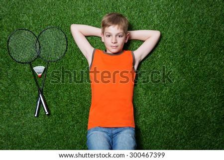 Boy lying with badminton racket on green grass - stock photo