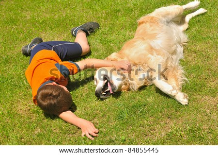 Boy lying with dog on green grass in park - stock photo