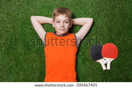 Boy lying with tennis racket on green grass - stock photo
