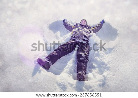 Boy making a snow angel - stock photo