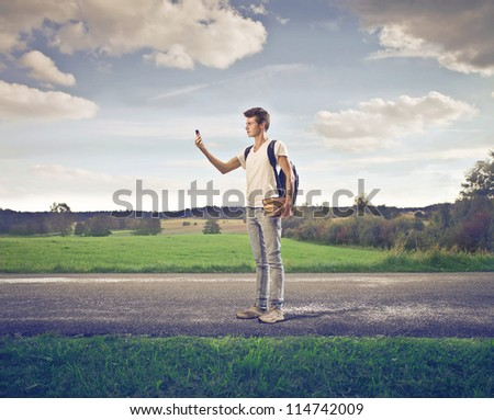 Boy making a video call on a countryside road - stock photo
