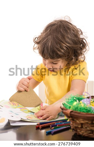 Boy making Easter decorations from carton paper against white background - stock photo