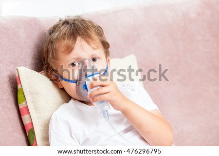 Boy making inhalation with a nebulizer at home