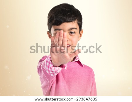 Boy making stop sign over ocher background