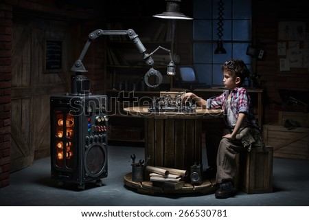 Boy mechanic robot helper playing chess in the studio in the evening - stock photo