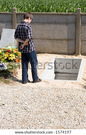Boy meditating in front of an open grave - stock photo