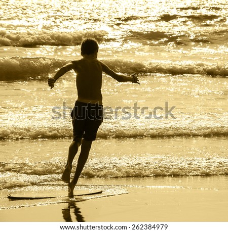 Boy moves on the surf board (alongside the sea shore) at sunset. Back view. (Brittany, France) Freedom concept. Aged photo. Sepia. - stock photo