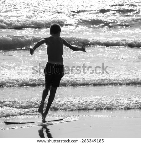 Boy moves on the surf board (alongside the sea shore) at sunset. Back view. (Brittany, France) Freedom concept. Aged photo. Black and white. - stock photo