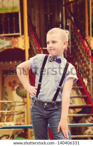 Boy near a game park attraction. A boy in a shirt with a stylish haircut and a butterfly. Boy waiting for a ticket to the roundabout. A boy wearing blue shirt and pants with suspenders. - stock photo