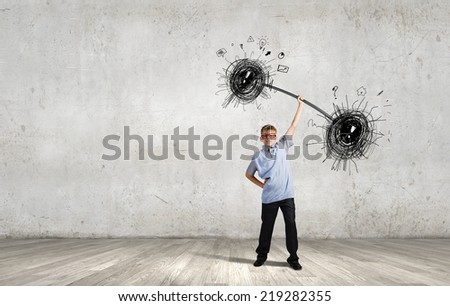 Boy of school age lifting barbell on one hand - stock photo
