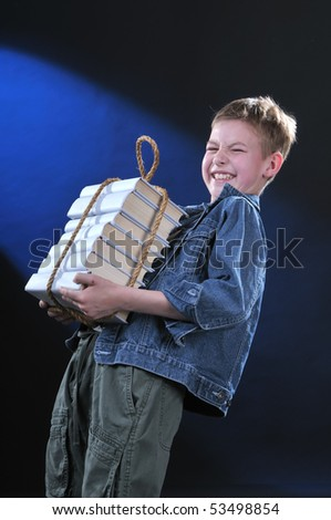 boy of ten years gets on the hip an exhausting load from the pile of books - stock photo