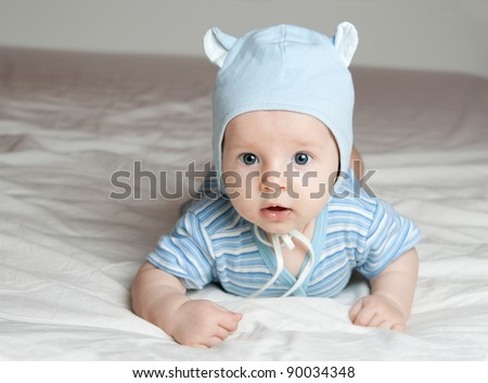 Boy of three months lies on the bed sheet