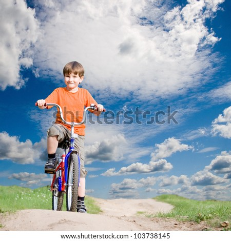 Boy on a bicycle on a background of blue sky - stock photo