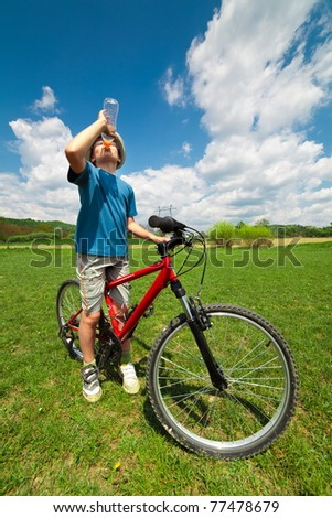 Boy on a bicycle stopped to have a break and drink water - stock photo