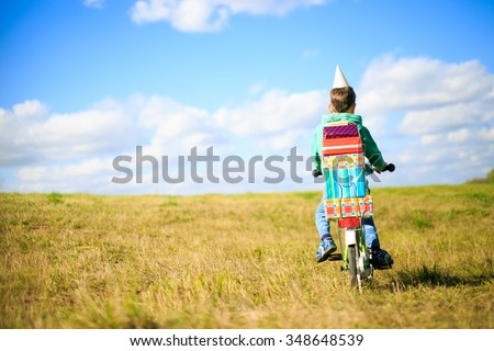 boy on a bicycle with a pile of gifts. on the bike a lot of gifts for his birthday. Boy rides a bicycle on the meadow, view from the back. copy space for your text - stock photo