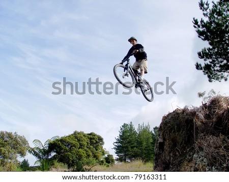 Boy on a bmx bike mid jump high in the air - stock photo