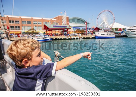 Boy on a  boat pointing (focus on boys arm) - stock photo