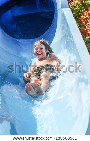 Boy on a tube going down a water slide - stock photo