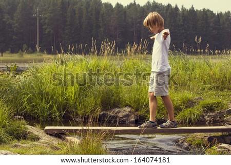 Boy on a wooden bridge - stock photo