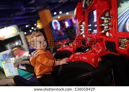 Boy on amusement bike at indoor playground - stock photo