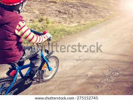 Boy on bike at gravel road in spring - stock photo