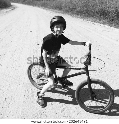 Boy on bike, black and white instagram effect - stock photo