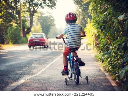Boy on bike on sidewalk - stock photo