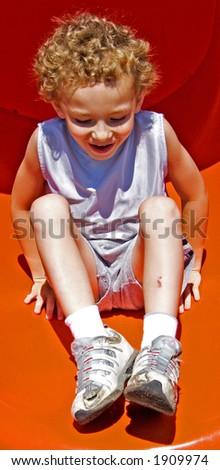Boy on bottom of slide - stock photo