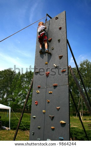 Boy on climbing wall - stock photo
