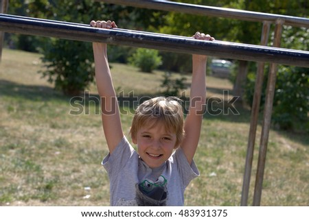Boy on parallel bars in the park
