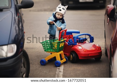 boy on parking with shopping carriage - stock photo