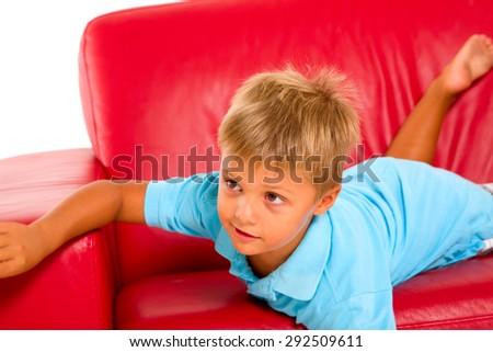 boy on red sofa - stock photo