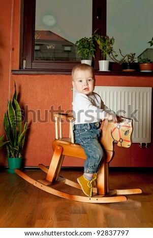 Boy on rocking horse - stock photo